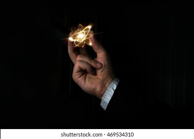 Scientist man holding atom particle between his fingers