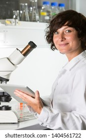 Scientist with microscope and tablet pc at the laboratory