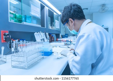 Scientist mix chemicals with The shake machine Before the experiment.Mixture laced with samples into test tubes,Thailand scientist working in the lab