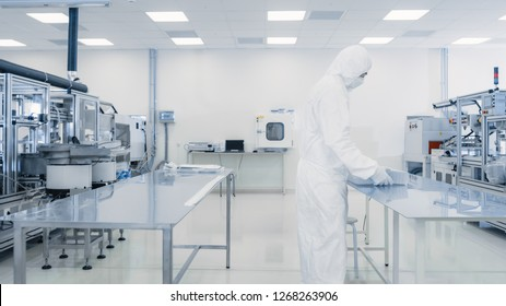 Scientist in Protective Suit Working with Case of Finished Product Through Laboratory. Workers in the Facility with Modern Industrial Machinery. Product Manufacturing Process: Pharmaceutics, Biotech.