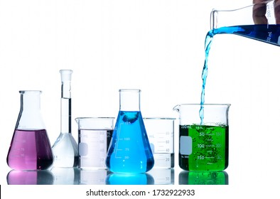 Scientist put blue liquid into measuring beaker  with laboratory glassware and liquids of different colors, Flasks and measuring beaker isolated on white background, Scientific equipment concept