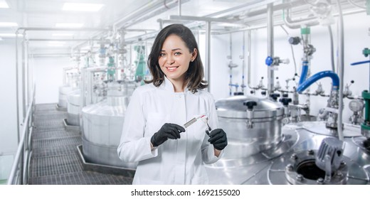 Scientist, researcher, microbiologist with a vaccine in a syringe against the background of drug production. Concept production of a vaccine during the covid-19 pandemic