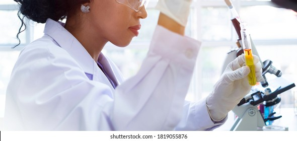 Scientist / researcher team conducting scientific research in science lab. African female scientist / researcher working on R&D project for bio chemistry. African scientist in hospital lab concept.