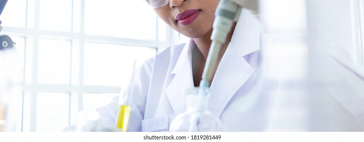 Scientist / researcher team conducting scientific research in science lab. African female scientist / researcher working on R&D project for bio chemistry. African scientist in lab concept. Banner.
