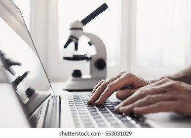 Scientist or student using  laptop computer and microscope