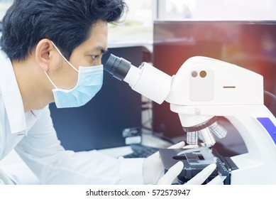 Scientist using microscope for analysis experiment medicine and chemistry sample test at biotechnology laboratory
