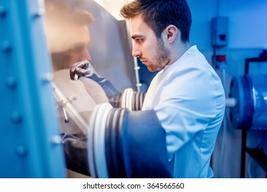 Scientist using protective robber gloves for handling dangerous substances in sterile environment