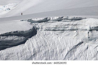 A scientist walks close to the edge of a glacier ice cliff in the Antarctic Peninsula