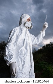 Scientist wearing a chemical protection suit takes a sample of contaminated water. On a background of sky.