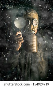 Scientist wearing a gas mask and holding a magnifying glass in a snow storm conducting research into the effects of gases, pollutants and carbon on climate change