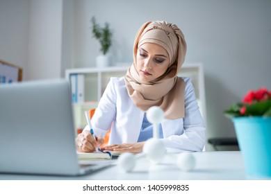 Scientist working hard. Female appealing chemical scientist working hard while using laptop and writing