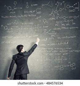 Scientist writing formulas on chalkboard