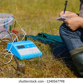 The scientist is writing in his notebook the data from a measuring device. The ecologist and his scientific equipment are in a natural ecosystem.