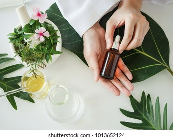 the scientist,dermatologist with the organic natural product in the laboratory.research and development beauty skincare concept.blank package,bottle,container .cream,serum.hand.