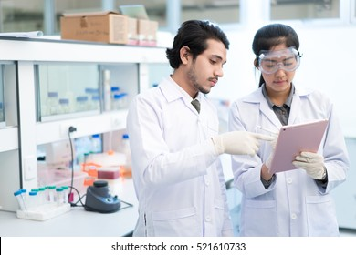 Scientists asian in the laboratory they use a tablet recording the results.