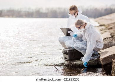 Scientists or biologists wearing protective uniforms working together on water analysis. Ecology and environmental pollution concept.