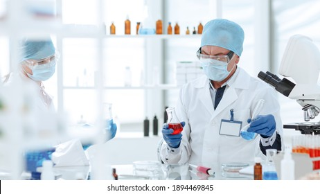 scientists colleagues checking the liquid in laboratory flasks.