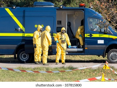 Scientists dosimetrists in protective clothing, gas masks and geiger counter near first response emergency bus with mobile laboratory in dangerous radioactive zone, Sofia, Bulgaria, November 6, 2015.