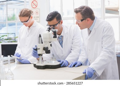 Scientists examining something with the microscope in the laboratory
