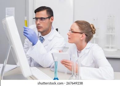 Scientists examining yellow precipitate in tube in the laboratory