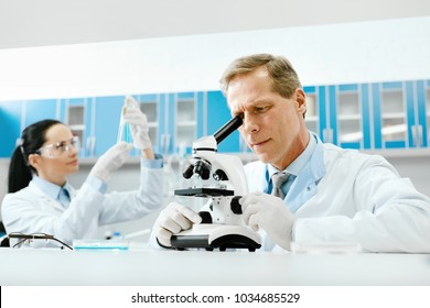 Scientists In Laboratory. Medical Workers At Work. Mature Male Doctor Researching Using Microscope While Female Scientist Working With Tubes In Modern Laboratory. Medical Lab. High Quality
