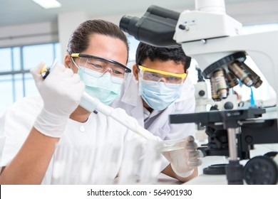 scientists male and female with equipment and science experiments ,laboratory glassware containing chemical liquid for design or decorate science or other your content and selective focus