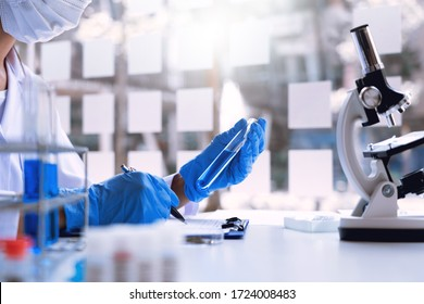 scientists researching in laboratory in white lab coat, gloves analysing, looking at test tubes sample, biotechnology concept.