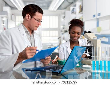 Scientists, senior Caucasian male and young African female, work with a microscope in research facility. Shallow DOF, focus on the face of the girl.