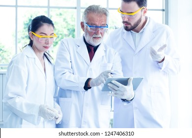 Scientists team are working or trying to evaluation or experiment for medical chemistry solution in laboratory and meeting in font the board