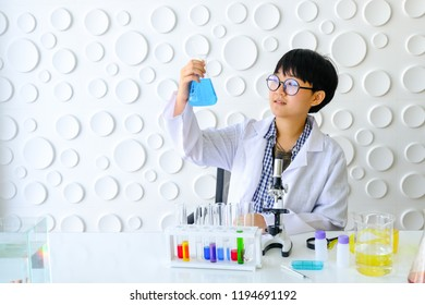 Scientists are working in laboratory. Young female researcher and her are doing investigations with test tubes.