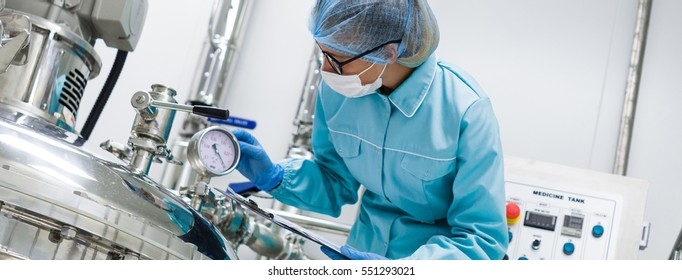 Scientists working with large vat in the lab, panoramic photo