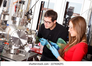 Scientists working with laser deposition chamber