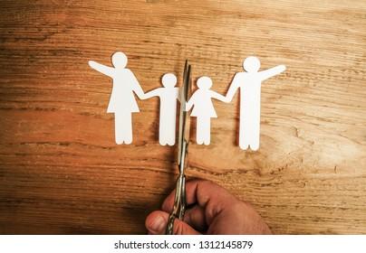 scissor divides the whole family. divorce idea. wooden figure. wood background.