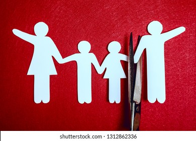 scissor divides the whole family. divorce idea. paper figure. red texture background.