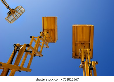 Scissor lift platform, cherry picker, aerial platform with bucket, three yellow construction machines and cranes, heavy industry, blue sky on background, bottom view