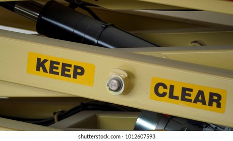 A scissor lift warning sign, keep clear