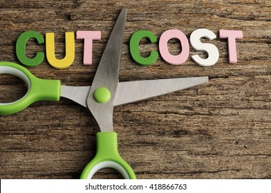 Scissors With CUT COST Word On Wooden Background