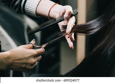 Scissors cut the girls hair, brunette