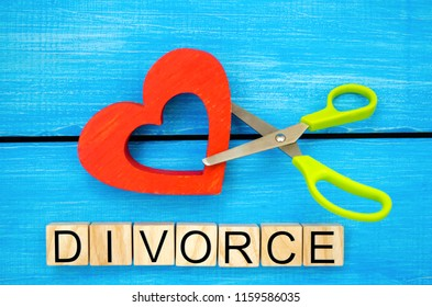 """scissors cut heart. the inscription """"divorce"""". the concept of breaking relations, quarrels. treachery, betrayal. cancellation of marriage. relationship problems. blue background"""