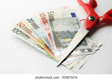Scissors cuts different euro banknote on table