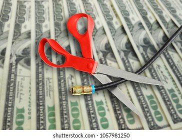 Scissors cutting a coax cable on cash background -- cutting the cord to save money concept