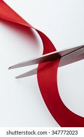 Scissors cutting a red ribbon.