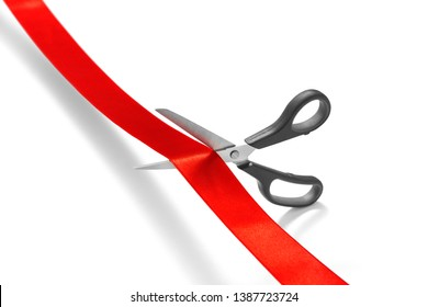 Scissors cutting red ribbon or tape against white background -Clipping Path