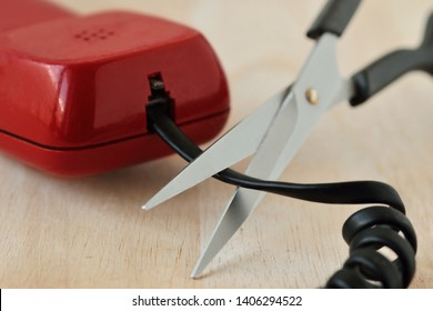 Scissors cutting telephone cord - Concept of landline phone