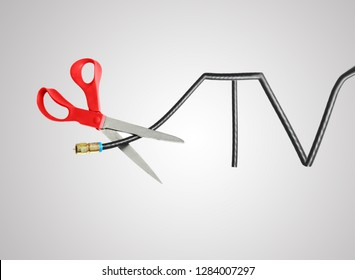 Scissors cutting through a TV shaped coaxial cable, cord cutting concept