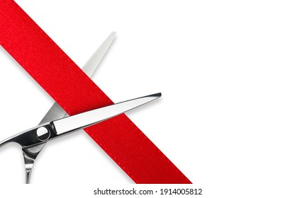 Scissors Grand opening. Top view of scissors cutting red silk ribbon against white isolated background with copy space. Silver stainless metal scissors or shears.