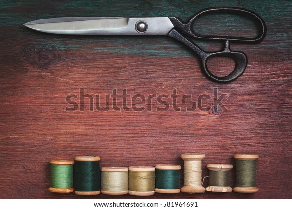 scissors and old threads on old wooden background in vintage style (top view, toning)