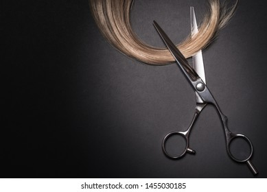Scissors and piece of blond hair. Professional barber hair cutting shears on black background. Hairdresser salon equipment concept, premium hairdressing set. Accessories for haircut with copy space