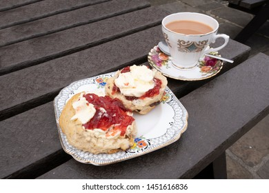 Scone with jam and cream, half with cream first, the other with jam first, with a cup of tea in vintage china, a british argument or dilemna whether to put the jam or the cream on the scone first