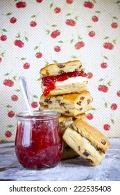 Scones with cherry jam / marmalade and cream with and cherry background